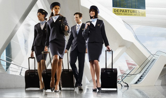 Male and female cabin crew walking through large modern airport building --- Image by © Matt Bird/Corbis